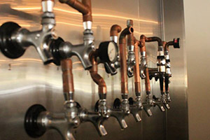 The stainless steel wall of beer taps at Lupulo